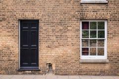 Zwarte voordeur op een herstelde bakstenen muur van een Victoriaans huis r Royalty-vrije Stock Foto