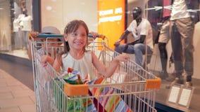 Zwarte vrijdag, rolt de vrolijke jongen meisje in aankopenkarretjes bij winkelcomplex voorbij winkelvensters van opslag stock footage