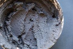 Zwarte vulkanische kosmetische klei in een kom kosmetische dichte omhooggaand van de kleitextuur oplossing van kosmetische klei a stock fotografie