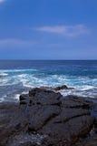 Zwarte vulkanische rotsen op oceaankust Royalty-vrije Stock Foto's