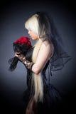 Zwarte weduwe in zorg met bloemen met een sluier Stock Foto's