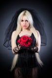 Zwarte weduwe in zorg met bloemen met een sluier Stock Foto