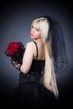 Zwarte weduwe in zorg met bloemen met een sluier Stock Fotografie