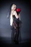 Zwarte weduwe in zorg met bloemen met een sluier Royalty-vrije Stock Afbeeldingen