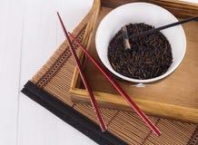 Zwarte wilde rijst in een ceramische kom met eetstokjes op een oosterse bamboeachtergrond Royalty-vrije Stock Afbeeldingen