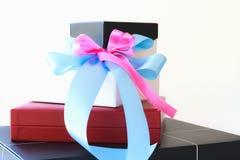 Zwarte witte en rode giftdoos met blauwe en roze lintboog Stock Afbeelding