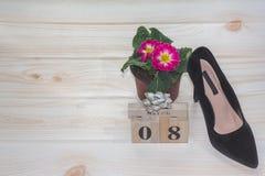 Zwarte women& x27; s schoenen tegen 8 Maart Gehielde schoenen en houten kalender stock afbeeldingen