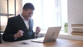 Zwarte Zakenman Celebrating Success terwijl het Werken aan Laptop stock videobeelden
