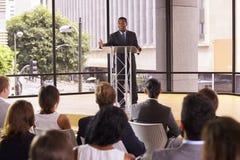 Zwarte zakenman die bedrijfsseminarie voorstellen aan een publiek stock afbeelding