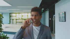 Zwarte zakenman die op telefoon spreken Knappe Afrikaans-Amerikaanse mens in kostuum die telefoongesprek in bureau het kijken heb stock footage