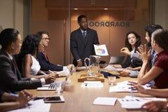 Zwarte zakenmantribunes om aan collega's op vergadering voor te stellen royalty-vrije stock afbeeldingen
