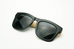 Zwarte zonnebril met houten benen op witte achtergrond Stock Foto