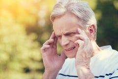 Zwarzony starsza osoba mężczyzna cierpienie od migreny Zdjęcia Royalty Free