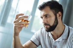 Zwarzony uzależniony mężczyzna trzyma szkło z whisky obrazy stock