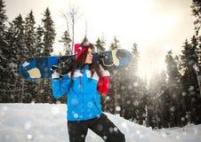 Zweckmäßige Frau mit Snowboard im Schneefallwinter auf Kiefer Stockbild