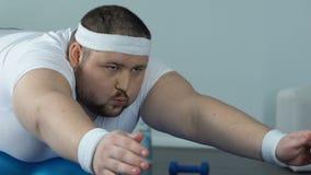 Zweckmäßiger fetter Mann, der die statische Übung liegt auf Eignungsball, Wunsch zur Schau zu tragen tut stock video