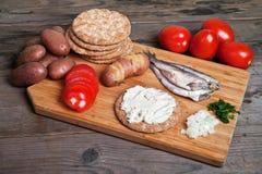 Zweedse haringen en ingrediënten op scherpe raad Royalty-vrije Stock Afbeeldingen
