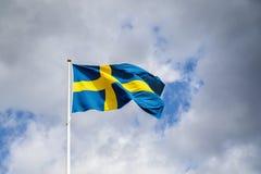 Zweedse vlag met wolken en hemelachtergrond Stock Foto's