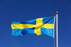 Zweedse vlag in wind tegen de hemel Stock Foto