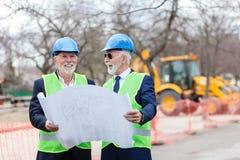 Zwei ältere Architekten oder Teilhaber, welche die Baustelle, Gebäudepläne betrachtend besichtigen lizenzfreie stockfotografie