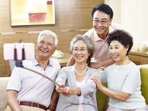 Zwei ältere asiatische Paare, die ein selfie nehmen Stockfotos