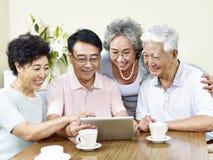 Zwei ältere asiatische Paare unter Verwendung des Tablet-Computers stockbild
