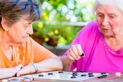 Zwei ältere Damen, die Brettspiel im Erholungsheim spielen Stockbilder