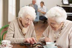 Zwei ältere Frauen, die Dominos spielen Stockfoto