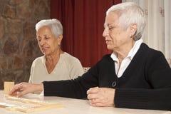Zwei ältere Frauen, die Dominos spielen stockfotos