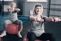 Zwei ältere Frauen, die heraus Hände mit Dummköpfen ausdehnen stockbild
