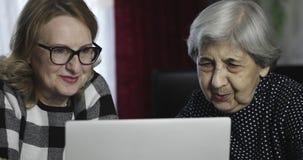 Zwei ältere Frauen stehen durch das Internet auf dem Computer in Verbindung stock video footage