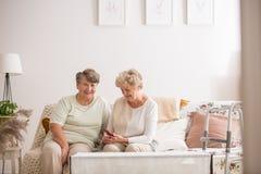 Zwei ältere Freunde, die zusammen an der Couch sitzen stockfotografie