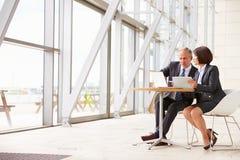 Zwei ältere Geschäftskollegen bei der Sitzung im modernen Innenraum lizenzfreie stockbilder