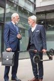 Zwei ältere Geschäftsmänner, die vor einem Bürogebäude sprechen lizenzfreie stockfotos