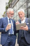 Zwei ältere graue behaarte Geschäftsmänner, die vor einem Bürogebäude sprechen stockfotografie