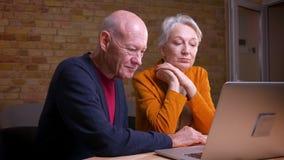Zwei ältere grauhaarige kaukasische Gatten sprechen im videochat auf dem Laptop, der interessiert und aktiv ist stock video