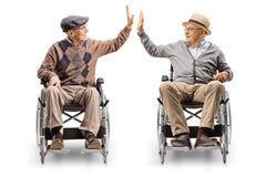 Zwei ältere Männer beim Rollstuhlgeben hoch--fünf stockbild