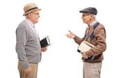 Zwei ältere Männer, die Bücher und die Unterhaltung halten lizenzfreie stockfotografie