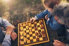 Zwei ältere Männer, die Spaß haben und Schach am Park spielen Stockfoto