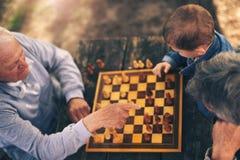 Zwei ältere Männer, die Spaß haben und Schach am Park spielen Stockfotografie