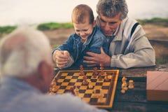 Zwei ältere Männer, die Spaß haben und Schach am Park spielen Lizenzfreies Stockbild