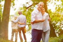 Zwei ältere Paare im Garten im Sommer Stockfotografie