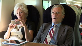Zwei ältere Wirtschaftler, die auf Zug austauschen stock video footage