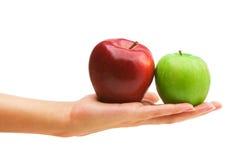 Zwei Äpfel auf einer Hand Stockfotos