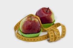 Zwei Äpfel in den Backencup Stockfotografie
