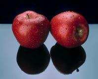 Zwei Äpfel mit schwarzer Reflexion. Lizenzfreies Stockfoto