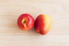 Zwei Äpfel sind auf dem Holztisch Stockbilder