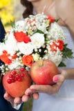 Zwei Äpfel und ein Brautblumenstrauß Stockbild