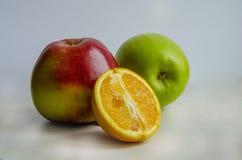 Zwei Äpfel und eine Orange Stockfotos
