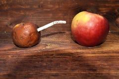 Zwei Äpfel und Zigarette im hölzernen Hintergrund kranker Mann mit Zigarette Lizenzfreies Stockbild